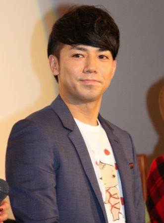 ジャケットの中にかわいいイラストキャラクターのプリントTシャツを合わせたコーデの綾部祐二さん